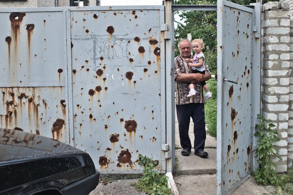 Marco Fieber Ein Großvater hält seine Enkeltochter in Stanyzja Luhanska im Arm. Am Tor zu sehen: zahlreiche Einschusslöcher.