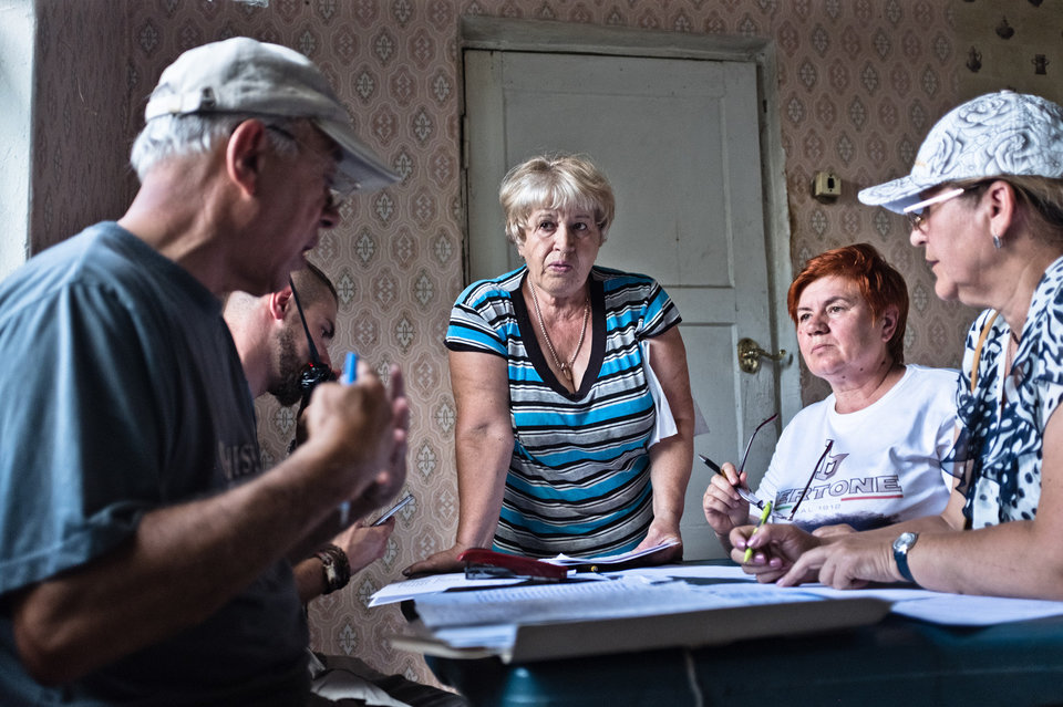 Marco Fieber Bewohner einer Ferienhaus-Siedlung (Datschen-Siedlung) in Schtschastja bei der Vergabe von humanitären Hilfspaketen.